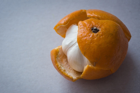 Expecting to see a sweet mandarin, we find under the skin bitter garlic. Pretense, hypocrisy, vain expectations, bitter essence under a beautiful wrapper. Light background. Stock Photo