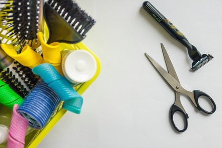 In the dustbin curlers and hairbrushes. Next scissors and a razor. A simple, radical, cardinal solution. Light background, top view.