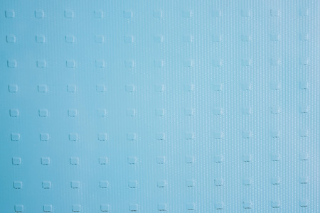 Blue glass, shiny surface, drawing in a shallow square. Glass texture, calm background.