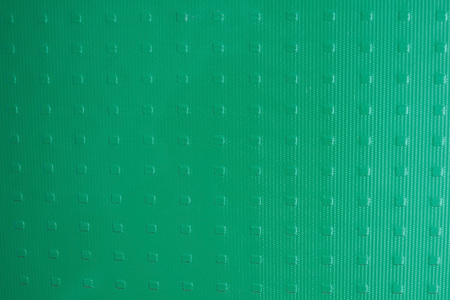 On a light frosted glass, a neutral pattern in a shallow square. Green, turquoise hue. Daylight. Stock Photo