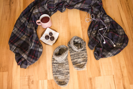 A warm plaid, a mug of tea and woolen socks are waiting for their master. Exit the comfort zone. Wooden background, top view.