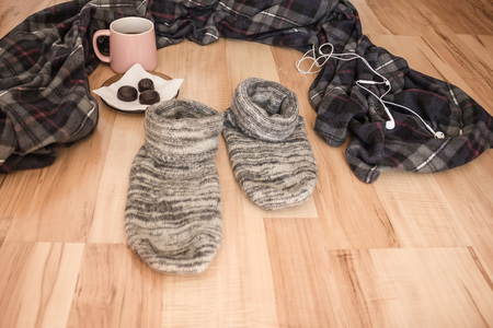 Plaid plaid, woolen socks for home mating, ceramic mug with tea and candy. Nobody here. Leave the comfort zone.