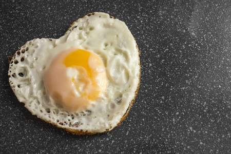 Simple recipes, homemade food. Fried egg in the form of heart. Heartily! Breakfast for the beloved. Dark background. Stock Photo