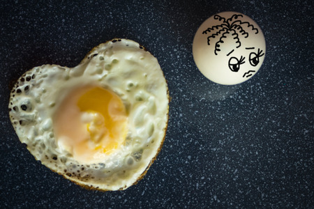 Fried egg in the form of heart. The second does not reciprocate. Love, undivided feelings, ardent passion. Dark background, the picture is made by the author.