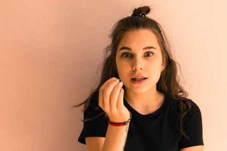 A surprised teenage girl in a black T-shirt. European appearance, long hair, eyes wide open, hand raised to the mouth. Light background, daylight.