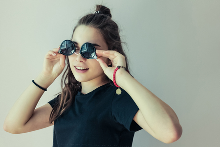On a light background a modern young girl, a teenager. In the hands of round sunglasses in black. Youth, carefree, fun.