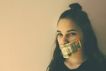 The girls mouth is glued to the dollar. Forced silence, bribery, unwanted witness. Green eyes, long hair. Muted tones, copy space. Stock Photo