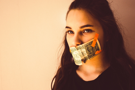 A young, modern girl, a teenager, is glued to the mouth with a dollar. Forced silence, unwanted witness. Eyes sad, look away. Toning, copy space.