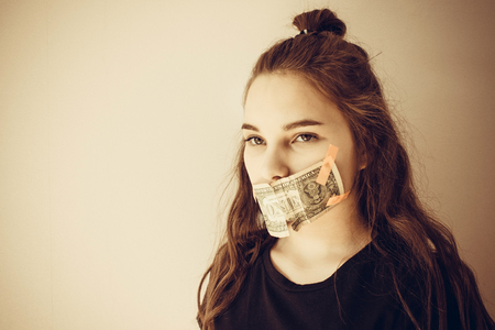 On a light background a teenage girl. The mouth is closed with money. Long hair, European type. Sad eyes look to the side. What do the children keep silent about?