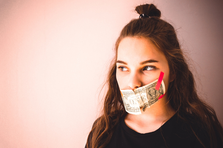 A young girl with European appearance, her mouth taped with small cash. Green eyes, a look to the side. Home secrets, skeletons in the closet. Copy space, toning.