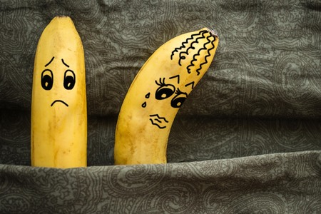 Two yellow bananas in bed, husband and wife. The couple turned their backs on each other, offended. Family problems, misunderstanding. The picture is made by the author. Stock Photo