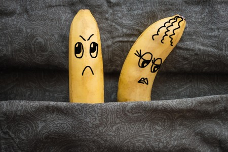 Spouses in a family bed, resent each other. Metaphor, two bananas - husband and wife. Dark background, daylight. The picture is made by the author.