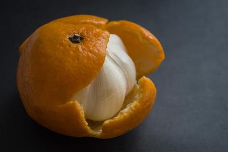 Bitter garlic bulb in tangerine skin. A hypocritical, evil man, a pretender concept photo. An unpleasant surprise, a trick, a deception. Dark background, side lighting.