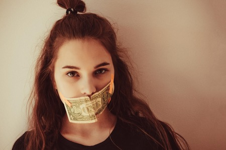 The girls mouth is sealed with money. Silence, family secrets, home terror. Green eyes, straight look. Toning, copy space.