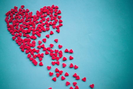 On a blue background a large red heart splits into pieces. Unhappy love, unrequited feelings, disappointment. Vignetting, copy space.