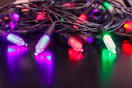 Color lanterns of an elongated shape shine in different colors. Defocus, blurry. Stock Photo