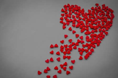 Unhappy love, undivided feelings, broken heart, loneliness. On a gray background, a large heart is scattered over the fragments. Vignetting, top view. Stock Photo