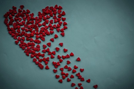 On a light background the red heart is scattered to pieces. Heart wound, bitter disappointment, unhappy love. Top view, vignetting.