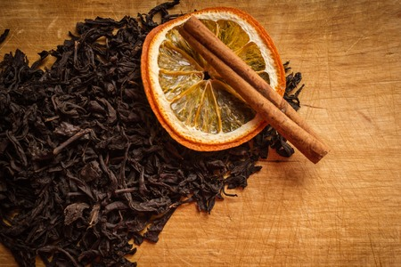 Old, wooden, kitchen table, top of the leaves of dry black tea, cinnamon and orange. Warmth, comfort, home cooking. Warm tones, vignetting.