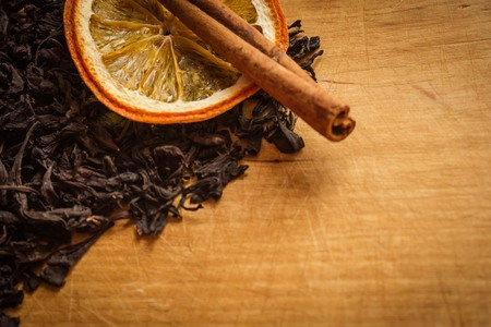 Black tea, a circle of orange and a stick of cinnamon. Aromatic tea with fruit additives. Home cooking, warmth and comfort. Vintage wooden background, vignetting.
