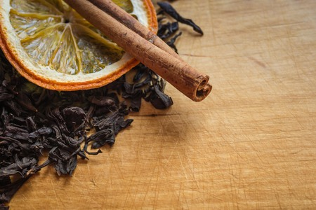 Cinnamon and a circle of orange on the black leaves of dry tea. Drink preparation, aromatic additives. Background natural wood, kitchen table with scratches from the knife. 版權商用圖片