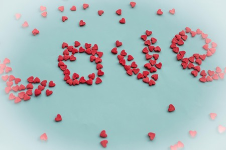 Against a blue background, the word love. Large letters are made of small red hearts. Top view, vignetting.