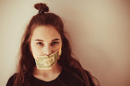 The girls face, European type, her mouth is closed with a small denomination. Fee for silence, an occasional witness, a victim of crime. Copy space, toning, vignetting.