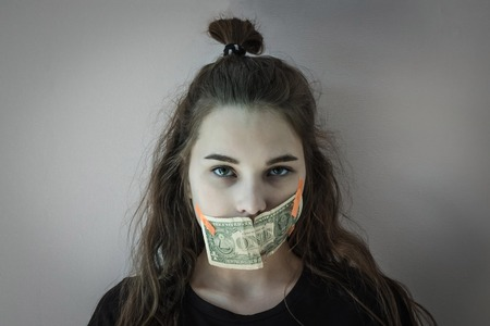 On a gray background a girl with long hair, her mouth taped with a cash bill. What do the children keep silent about? Domestic violence, incest, terror.