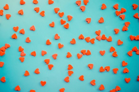 On a blue background there are little red hearts. Valentines Day, love, romance, tenderness, holiday. View from above.