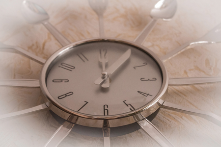 On light, modern, chrome, wall, kitchen clock, the hands show noon. Lunch time, diet, proper diet. Daylighting, vignetting.