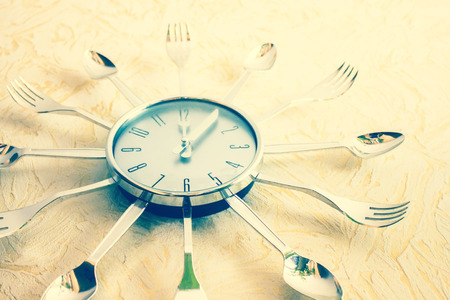 The dial has twelve hours, lunch time. Instead of the arrows there is a fork and a knife, cutlery along the circumference. Cooking, proper nutrition. Vintage toning. The product of mass production.