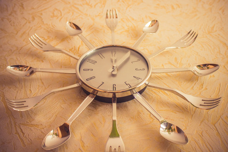On the yellow wall, a metal watch, the arrows show noon. Around the chrome spoons and forks. The right diet, food. Bottom view, vignetting. The product of mass production.