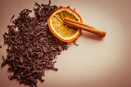 Black, dry leaves of tea, next to a circle of orange and a stick of cinnamon. A fragrant choice tea, a traditional drink. Light background, warm toning, vignetting, copy space. 版權商用圖片