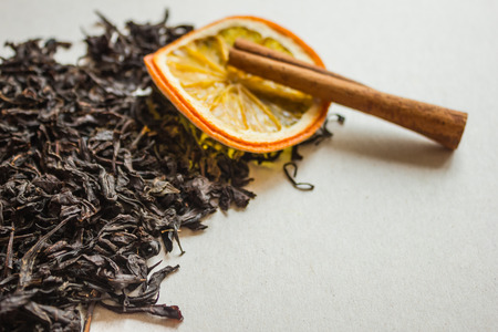 Selected leaves of fermented tea, a traditional drink. In the distance, orange and cinnamon, the background is blurred. Tea with aromatic additives, spices.