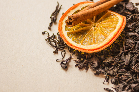 Ingredients for tea. Large leaves of the selected variety, dried orange and a stick of cinnamon. A fragrant drink, a symbol of hospitality. Copy space, warm toning.