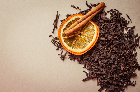 A stick of cinnamon, a circle of orange and large leaves of dry black tea. A fragrant drink with fruit additives, spices. Top view, light background, copy space.