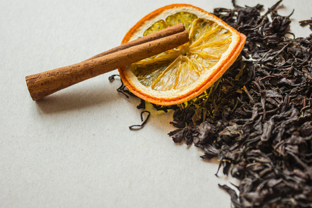 On a light background, large-leaf black tea, a circle of dried orange and a stick of cinnamon. Additives for tea, fragrant spices. Macro photography, copy space.