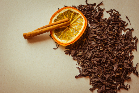 Traditional drink, flavored tea with additives. Large leaves of fermented tea, near an orange and a stick of cinnamon. Grocery, high quality goods.