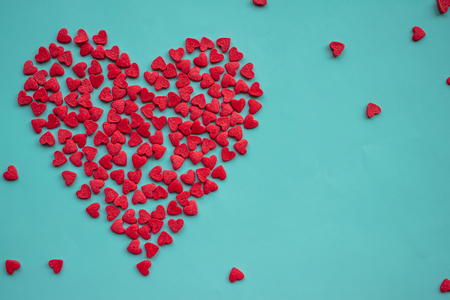 Valentine, a big red heart consists of many small ones. Blue background, daylight. A symbol of love, a tender feeling.