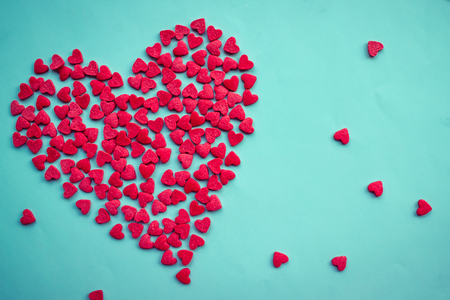 On a blue background there is one big heart and many small ones. Love, strong affection, recognition. Calm daylight, copy space. Stock Photo