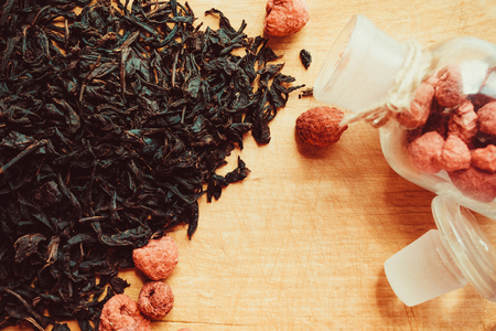 Black leaves of dry tea, next to dried raspberries in a glass container. A traditional hot drink, a symbol of home comfort. Daylight, vintage toning.