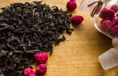 Ingredients for brewing black tea, cooking a traditional hot drink. Large, selected leaves of a tea tree, the highest grade. In a glass bottle, dried raspberries. Wooden background.