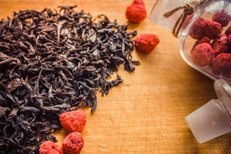 Dried red berries, raspberries, a fragrant additive to black tea. Traditional home cooking, coziness, hospitality. Natural wood background, old kitchen board.