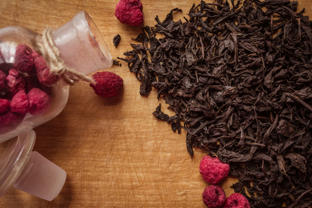 On the old kitchen board, collection, selected black tea, the highest grade. Next to the glass bottle with dried raspberries. Ingredients for making a hot drink.