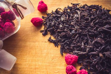 Fermented black tea, large dry leaves. Near raspberry, homemade preparations. Hospitality, comfort, home cooking. Daytime lighting, retro style. 版權商用圖片