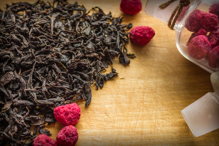 Traditional hot drink, aromatic tea with berry additive. Dried raspberries in a glass bottle, homemade billet. Large leaves of black tea on a wooden surface. Daylighting, vignetting.