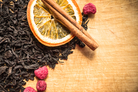 Black, choice tea, large dry leaves. Nearby fruit supplements. Wooden background with traces of a knife, a kitchen board. Copy space, vignetting. 版權商用圖片