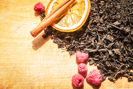 Home kitchen, old wooden table. Dry black tea, a circle of orange, a stick of cinnamon, red berries, raspberries. Bright sunlight, copy space.