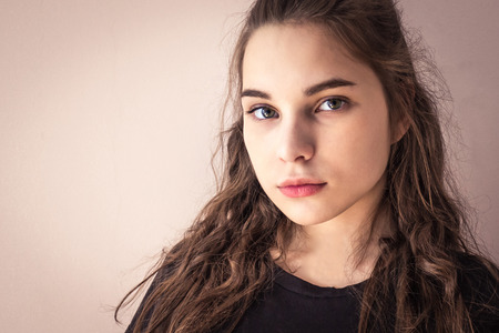 Portrait of a teenager, modern girl. European type of appearance, long hair, green eyes. Pleasant face, straight look. Light background, copy space.