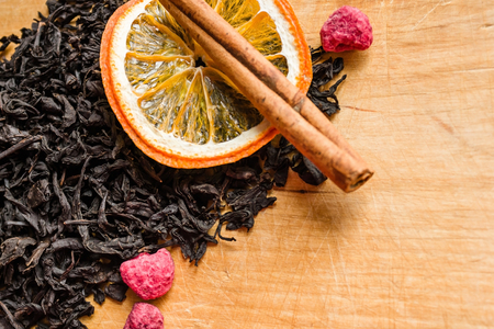 Dry black tea, collection grade. Near a stick of cinnamon, an orange slice and dried red raspberries. A fragrant drink, a symbol of hospitality, a traditional recipe.